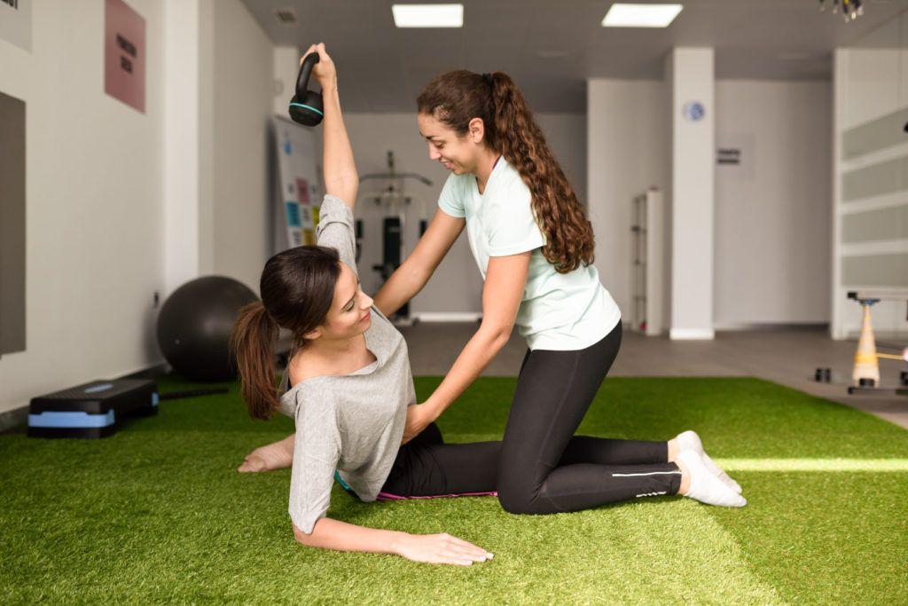 Physiotherapeutin mit Patentin bei Übungen am Gerät mit Hantel während der Rehabilitation im Physiotherapiezentrum in Kappeln.