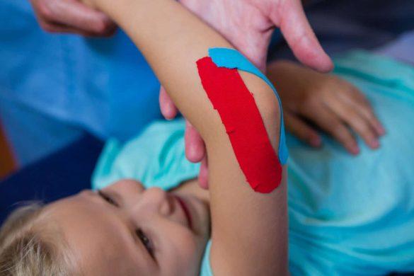 Physiotherapeut klebt Kinesio bei der jungen Patientin auf den Elbogen