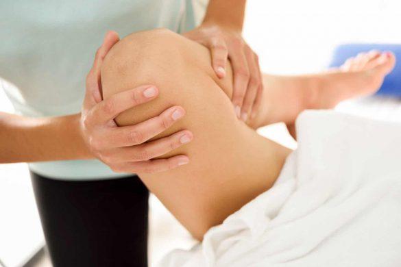Medizinische Massage am Bein in einem Physiotherapiezentrum. Weibliche Physiotherapeutin bei der untersuchung ihrer Patientin.